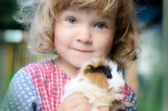 Nettes weißes Kleinkindmädchen in einem rustikalen Artkleid, das ein rotes Meerschweinchen auf ihren Händen hält lizenzfreie stockfotos