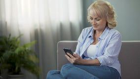 Nettes weibliches Sitzen von mittlerem Alter auf Couch und lustigen Fotos der Betrachtung am Telefon stock video footage