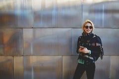 Nettes weibliches, Spaß bei der Stellung habend mit intelligentem Mobiltelefon gegen großen Wandhintergrund mit Kopienraum für fö Lizenzfreie Stockbilder