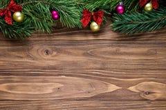 Nettes Weihnachtsthema auf dem hölzernen Hintergrund mit Kieferniederlassungen auf die Oberseite des Schirmes Lizenzfreie Stockbilder
