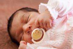 Nettes zwei-Wochen-altes neugeborenes Baby mit einem Friedensstifter Stockfotos