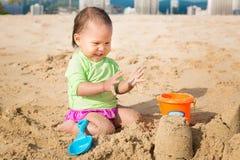 Nettestes Kleinkind, das mit Sandburg am Strand an einem sonnigen Sommertag spielt Stockbild