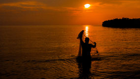 Netting In. A fisherman trying to catch fish using net at dusk nearby Port Dickson, Negeri Sembilan, Malaysia Stock Images