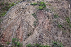 Netting over loose rocks. Details of netting over loose rocks to prevent landslip Royalty Free Stock Image