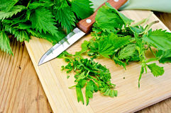 Nettle on the board with a knife and napkin Royalty Free Stock Photography
