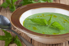 Nettle cream soup. On wooden background. Shallow dof royalty free stock images