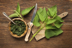 Nettle. Fresh green leaves on a wooden background stock image