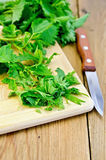 Nettle is incised on the board. Fresh green nettle incised on a wooden board with a knife Stock Images