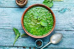 Nettle leaf soup. Nettle soup in bowl on wooden surface.Green nettle soup stock photo