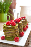 Nettle pancakes with raspberries. Traditional Scandinavian nettle or spinach pancakes with raspberries Stock Photos