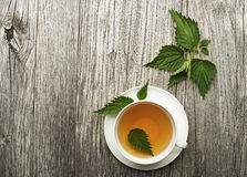 Nettle tea. Cup of healthy herbal tea with nettle on wooden background Stock Images