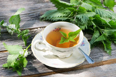 Nettle tea. Fresh nettle tea on wooden background stock photo