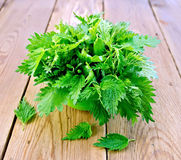 Nettles in a green bowl on board. Fresh green nettle in a bowl on a wooden boards background stock images