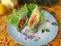 Nettles omelette roll stuffed with tomato and cheese. On a plate with lettuce, cooking vegetarian food with nettles and quail eggs stock image