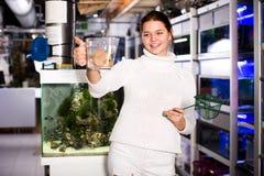 Netto fisk för flickauppehälleaquarian och vattenbehållare Royaltyfria Foton