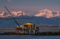 Netto fiskekoja för droppe på solnedgången mot fjällängarna med snö, Marina di Pisa, Tuscany, Italien royaltyfri foto