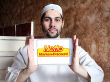Netto stores logo. Logo of the international chain of convenience stores netto on samsung tablet holded by arab muslim man Stock Image