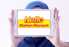 Netto stores logo. Logo of the international chain of convenience stores netto on samsung tablet holded by arab muslim woman Stock Photos