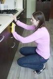 Nettoyage attrayant de fille sur la cuisine Photos libres de droits