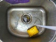 Nettoyage d'un évier avec l'éponge jaune Image libre de droits