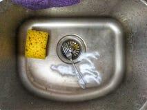 Nettoyage d'un évier avec l'éponge jaune et nettoyage de la poudre Images stock