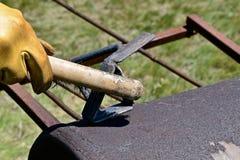 Nettoyage d'un fer de marquage à chaud avec une brosse métallique Photographie stock