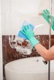 Nettoyage d'un verre de douche photographie stock libre de droits