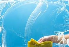 Nettoyage d'un vitrail avec le tissu jaune Photographie stock libre de droits