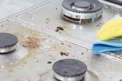 Nettoyage d'une cuisinière à gaz avec des ustensiles de cuisine, des concepts de ménage, ou hygiène et nettoyage image libre de droits