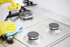 Nettoyage d'une cuisinière à gaz avec des ustensiles de cuisine, des concepts de ménage, ou hygiène et nettoyage images stock