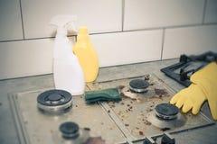 Nettoyage d'une cuisinière à gaz avec des ustensiles de cuisine, des concepts de ménage, ou hygiène et nettoyage photographie stock