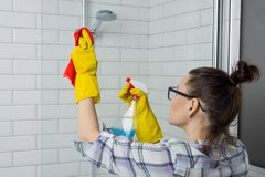 Nettoyage de Chambre Femme nettoyant la salle de bains, femelle dans des vêtements sport avec le détergent et le gant de toilette images stock