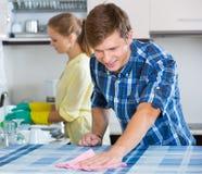 Nettoyage de couples dans la cuisine ensemble Images stock