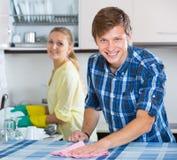 Nettoyage de couples dans la cuisine ensemble Photographie stock libre de droits