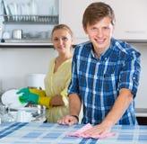 Nettoyage de couples dans la cuisine ensemble Image stock