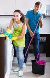 Nettoyage de couples de famille dans la cuisine ensemble et le sourire Image stock