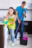 Nettoyage de couples de famille dans la cuisine ensemble et le sourire Images libres de droits