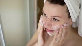 Nettoyage de femme se lavant le visage avec la mousse dans la salle de bains clips vidéos
