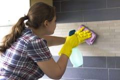 Nettoyage de jeune fille dans la cuisine Photo stock