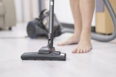 Nettoyage de jeune homme avec l'aspirateur à la maison image stock