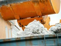 Nettoyage de la ville en hiver l'excavatorl jette la neige dans le camion image libre de droits