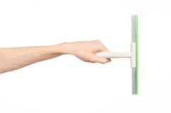 Nettoyage de ménage et thème de fenêtres de lavage : la main de l'homme jugeant des fenêtres d'un grattoir de vert d'isolement su photos libres de droits