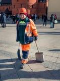 Nettoyage de territoire Femme dans des uniformes oranges nettoyer le trottoir dans le secteur de la place rouge photos libres de droits