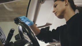 Nettoyage de voiture - la jeune femme attirante lave le fauteuil d'un véhicule de luxe avec une brosse, De-focalisé Photos stock