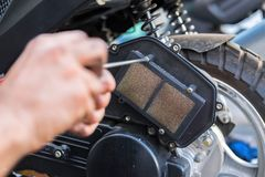 nettoyage du filtre à air, du scooter et de la moto, l'employee& x27 ; mains de s pendant l'entretien Photos libres de droits