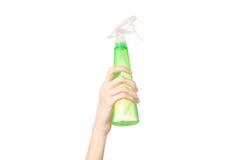 Nettoyage du thème de maison et de décapant : la main de l'homme jugeant une bouteille verte de jet pour nettoyer d'isolement sur Image stock
