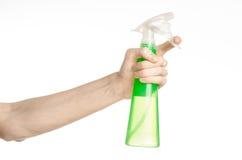 Nettoyage du thème de maison et de décapant : la main de l'homme jugeant une bouteille verte de jet pour nettoyer d'isolement sur Photographie stock