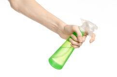 Nettoyage du thème de maison et de décapant : la main de l'homme jugeant une bouteille verte de jet pour nettoyer d'isolement sur Photographie stock libre de droits