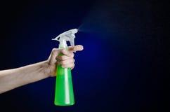 Nettoyage du thème de maison et de décapant : la main de l'homme tenant une bouteille verte de jet pour nettoyer sur un fond bleu Photos stock