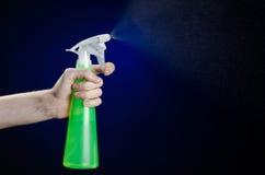 Nettoyage du thème de maison et de décapant : la main de l'homme tenant une bouteille verte de jet pour nettoyer sur un fond bleu Photographie stock
